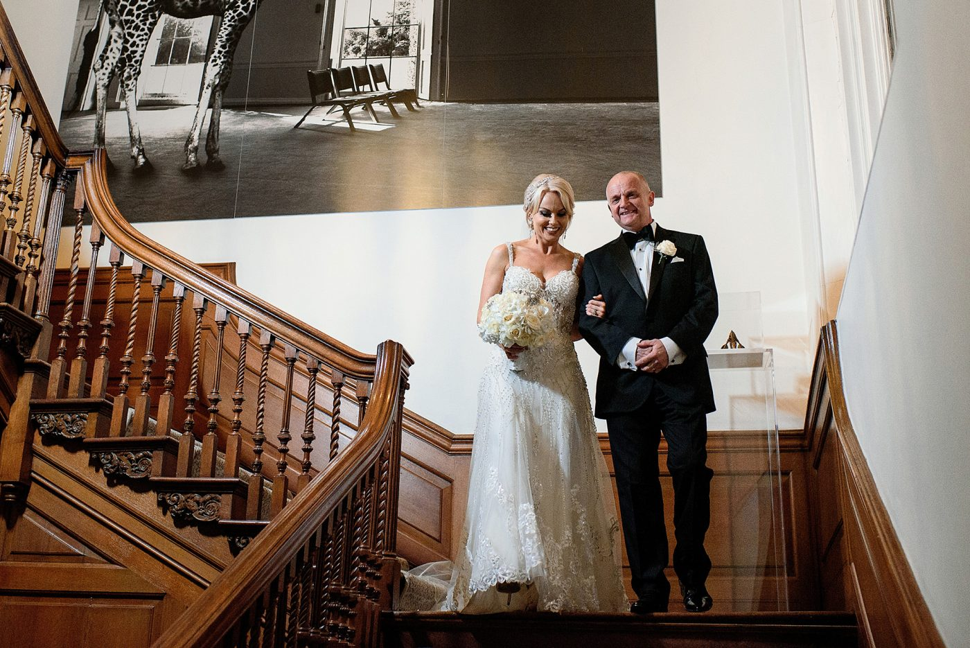 bride makes entrance with father on staircase in west wing