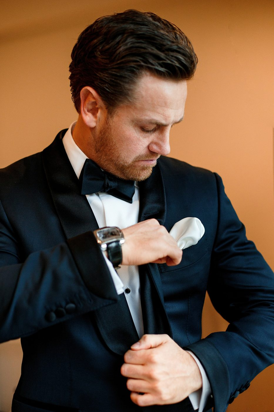 groom adjusting pocket square