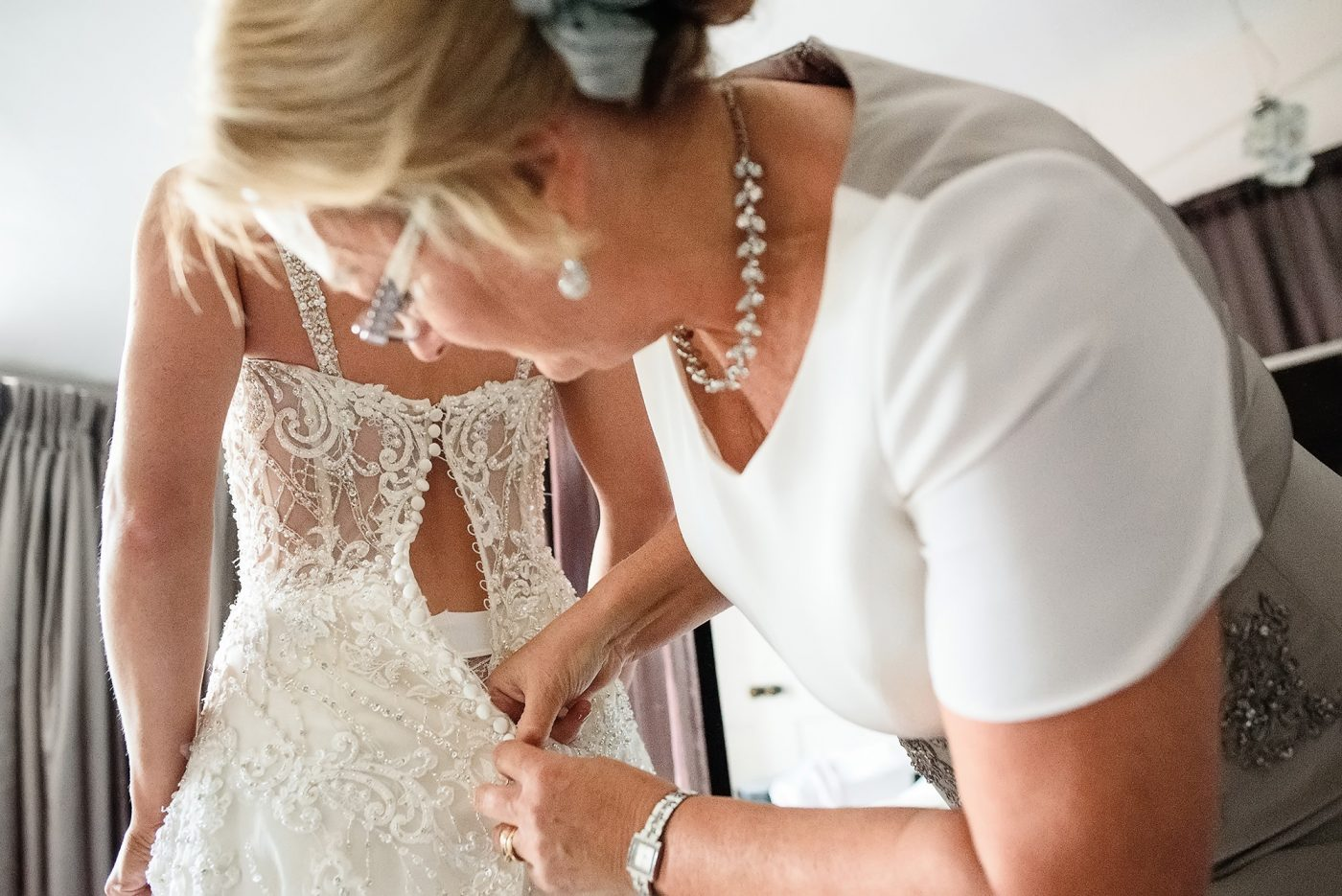 mother of the bride doing up dress