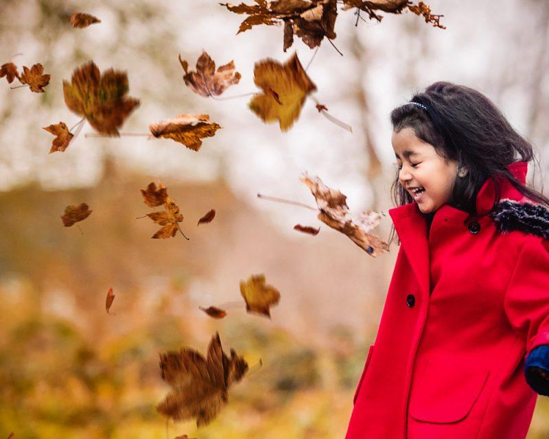 Girl kicking autumn leaves