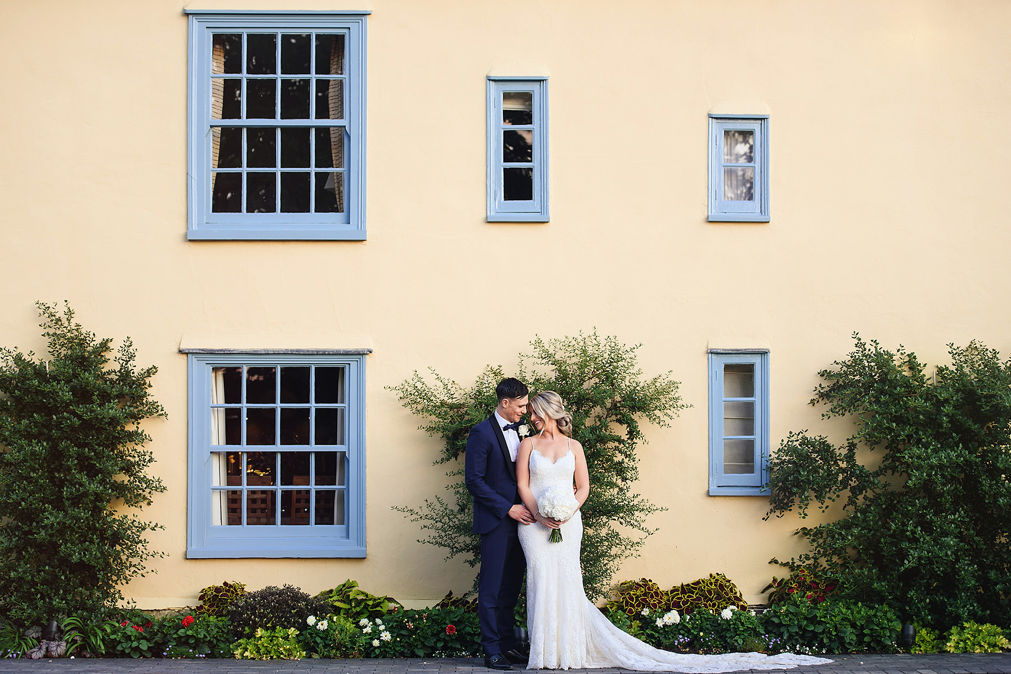 bride and groom portrait in front of farmhouse