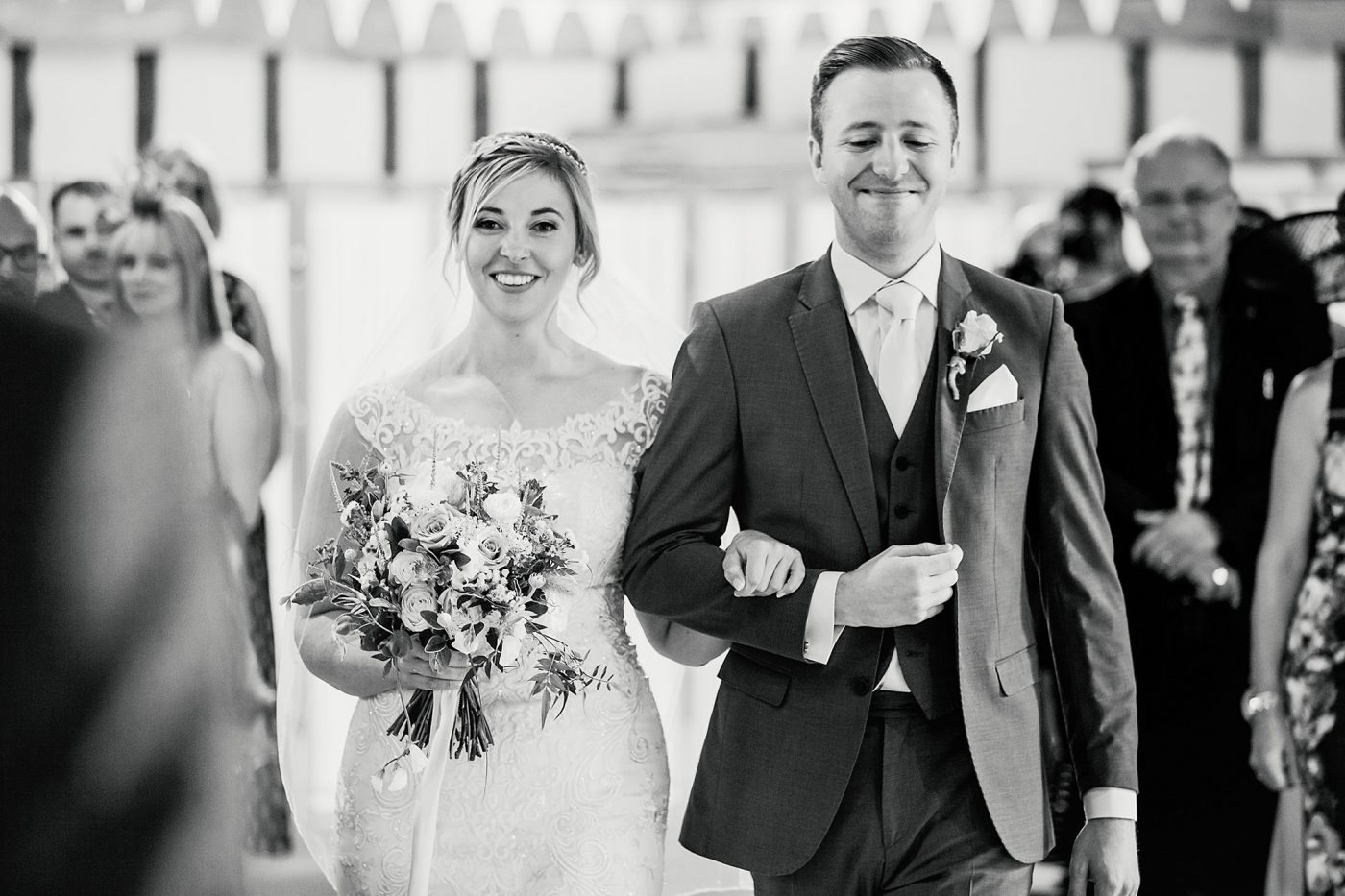 black and white picture of bride walking down the aisle