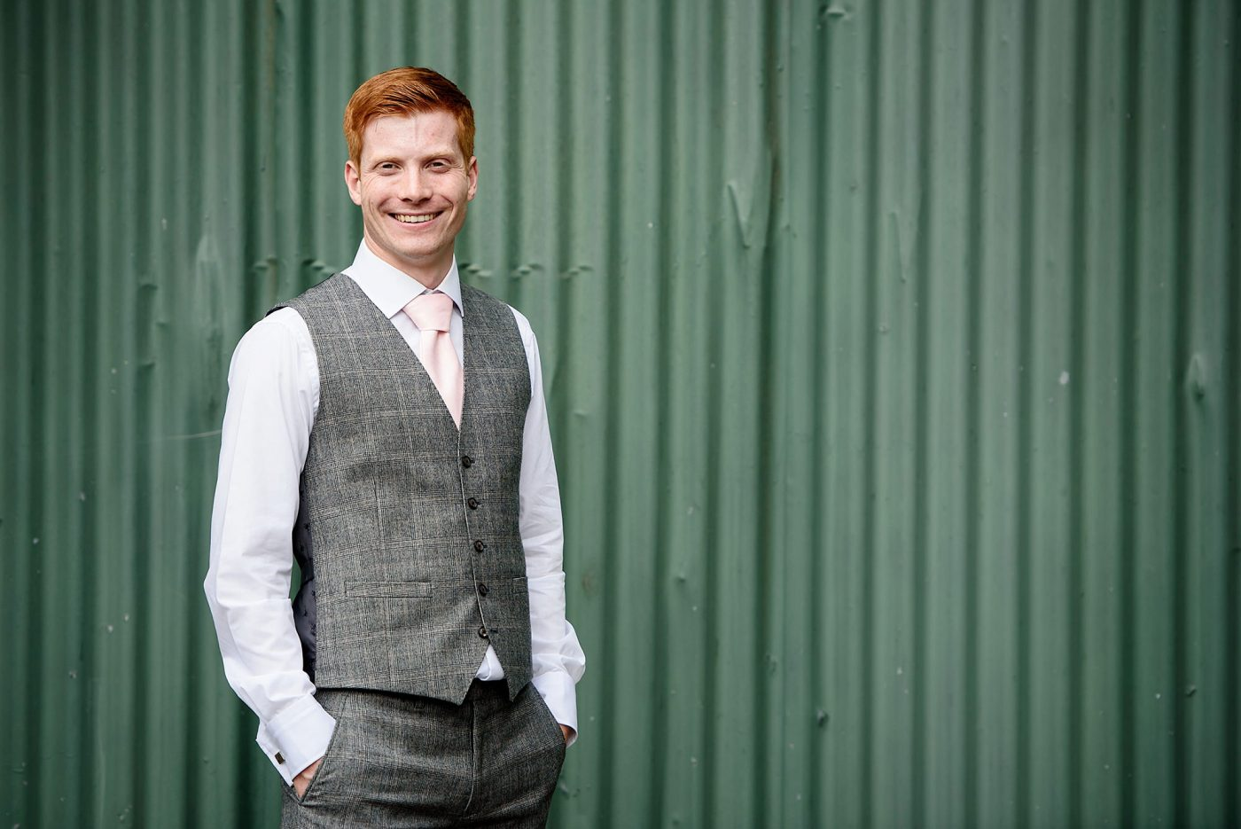 photo of the groom in front of green barn