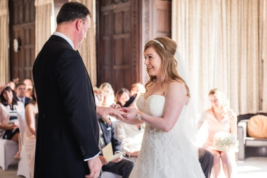 bride places ring on grooms finger