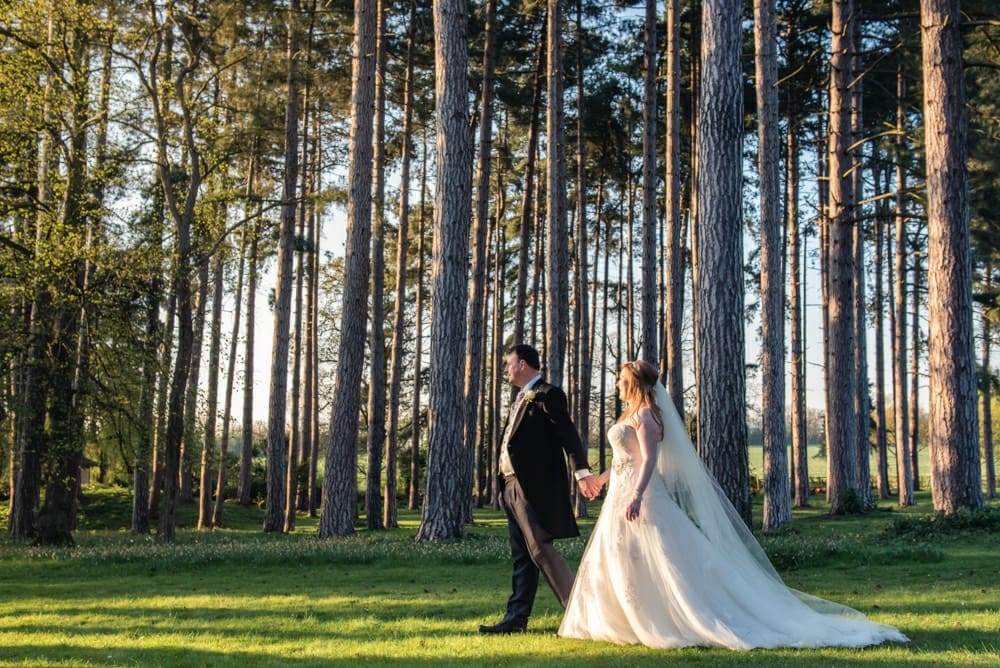 bride and groom walking through trees