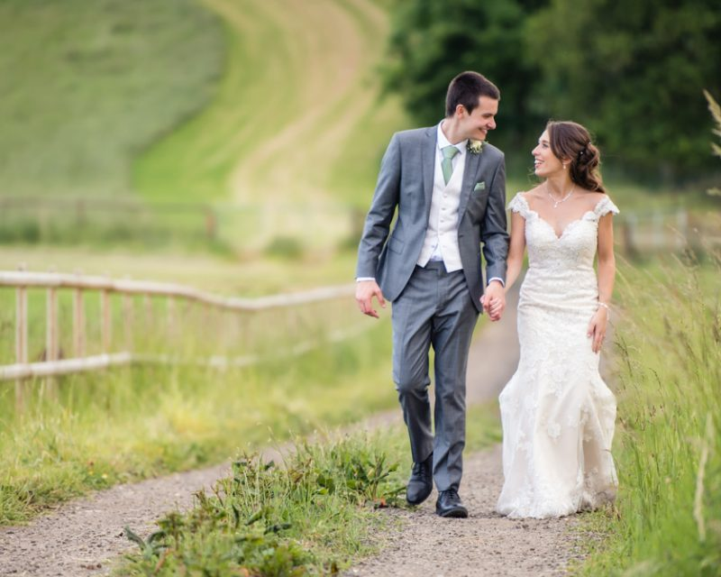 bride and groom walking through long grass on farm in pangbourne