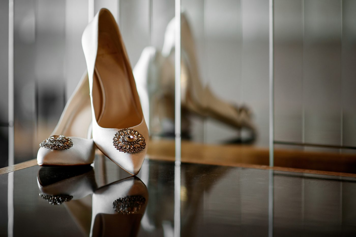 wedding shoes in front of mirrored wall