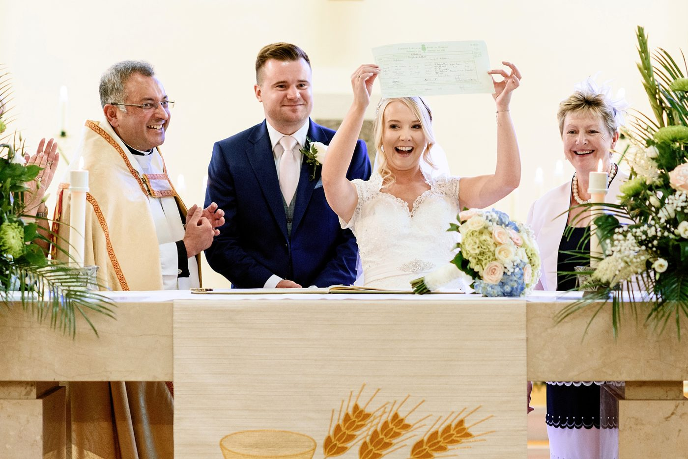 bride holds up marriage certificate