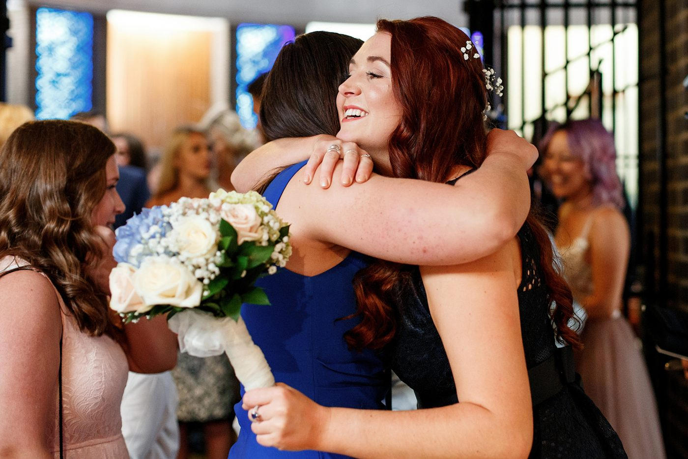 guests hugging at church wedding service