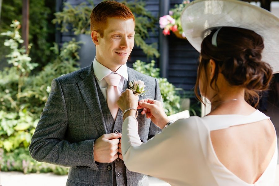 mother of the groom adjusting tie