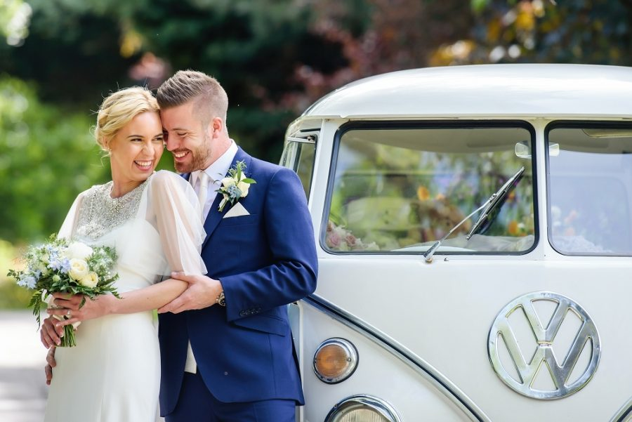 bride and groom laughing with vw camper