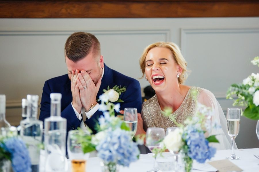husband and wife laughing at wedding
