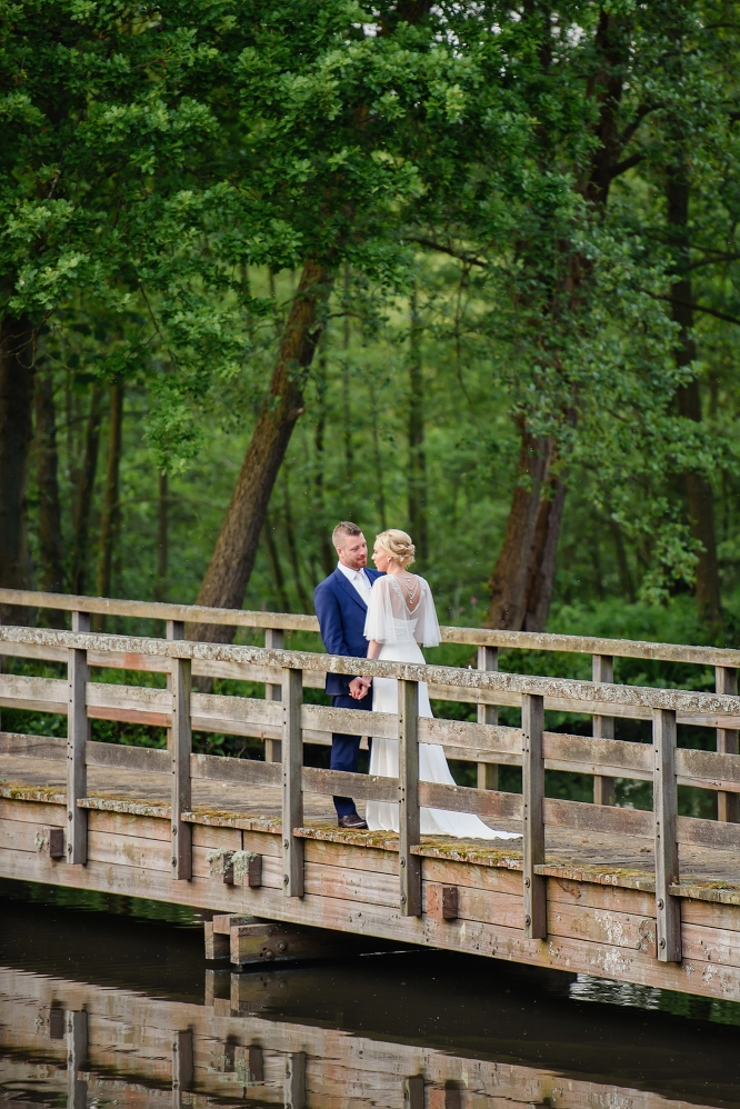 bride and groom stand on bridge at essendon country club