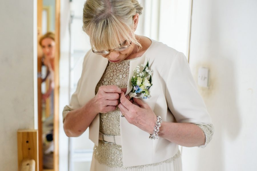 mother of the bride pins her flower