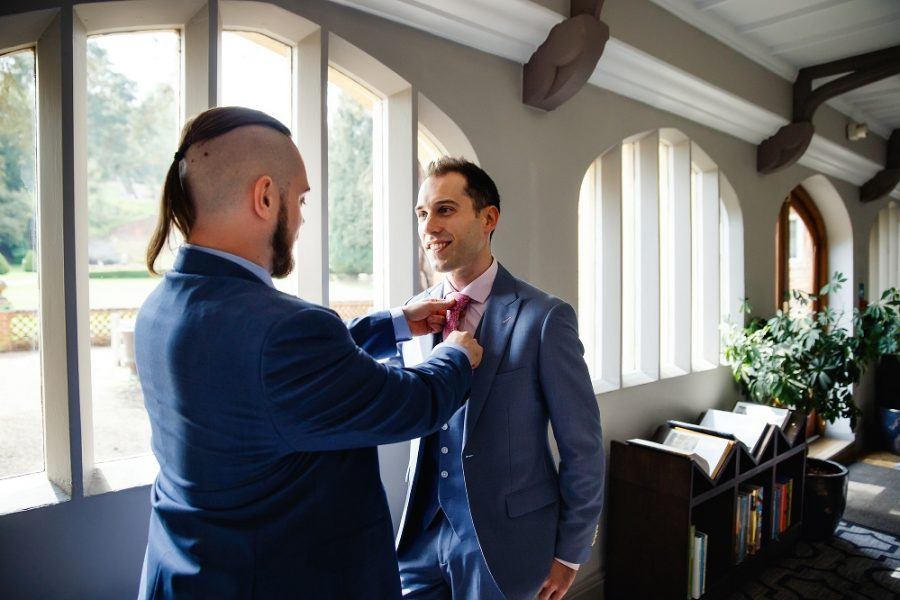 usher adjusting grooms buttonhole