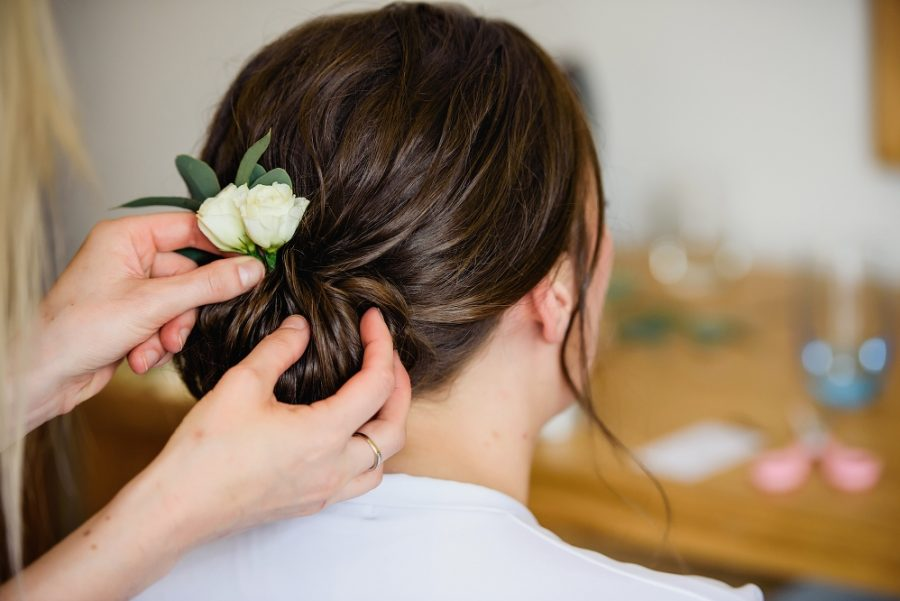 hairdresser putting flower in brides hair