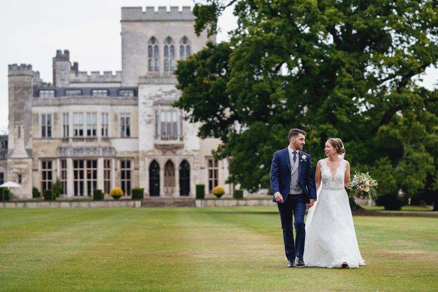 bride and groom walking with ashridge wedding venue in the background