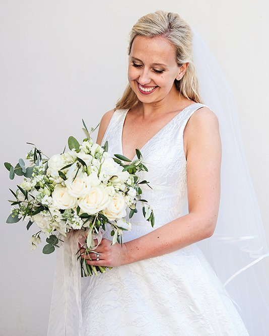 bride smiling and looking at bouquet