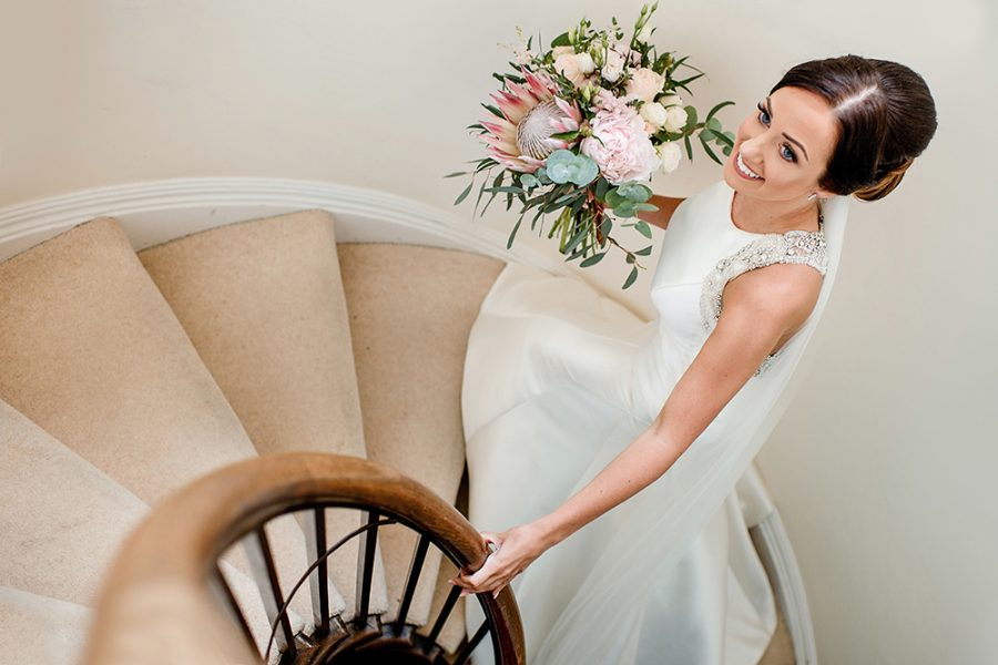 Bride walking upstairs with flowers