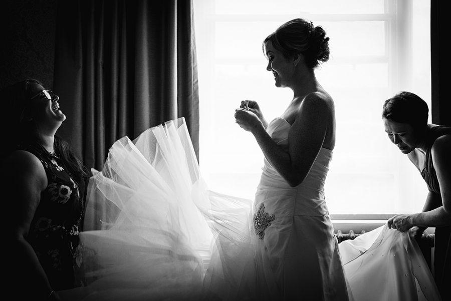 bridesmaids fluffing the wedding dress