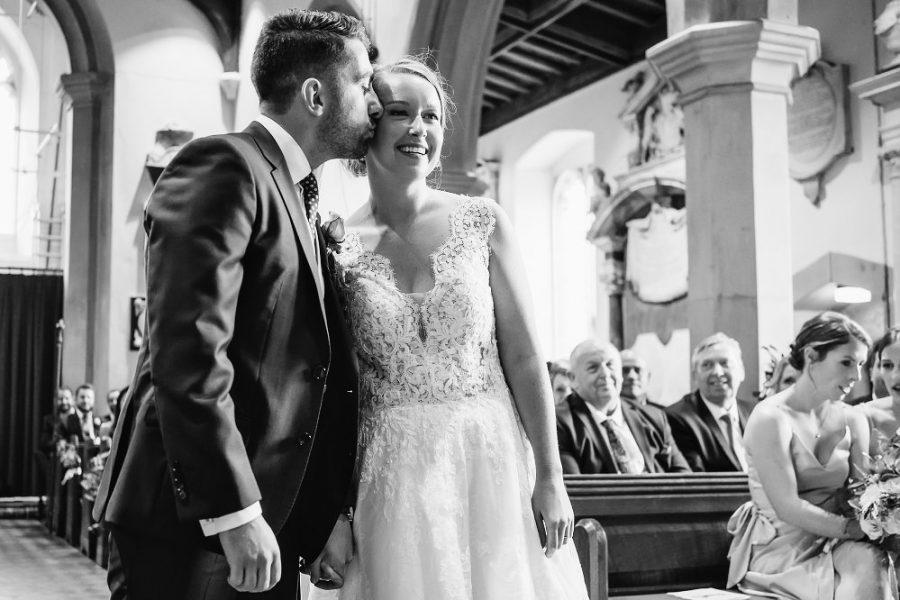 groom kisses bride at church wedding