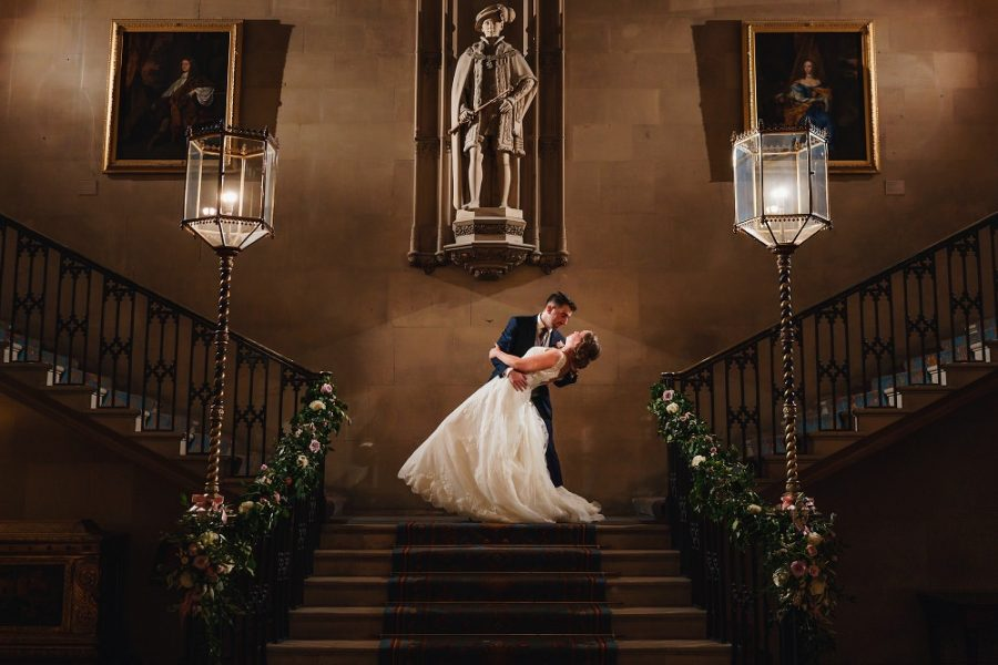 bride and groom kissing on the staircase at ashridge house