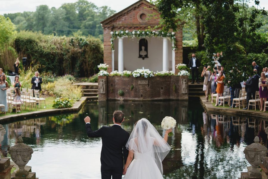 bride and groom wave to guests at Lakeside wedding ceremony