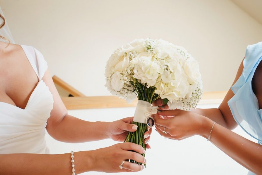 bridesmaids tying locket on the bouquet