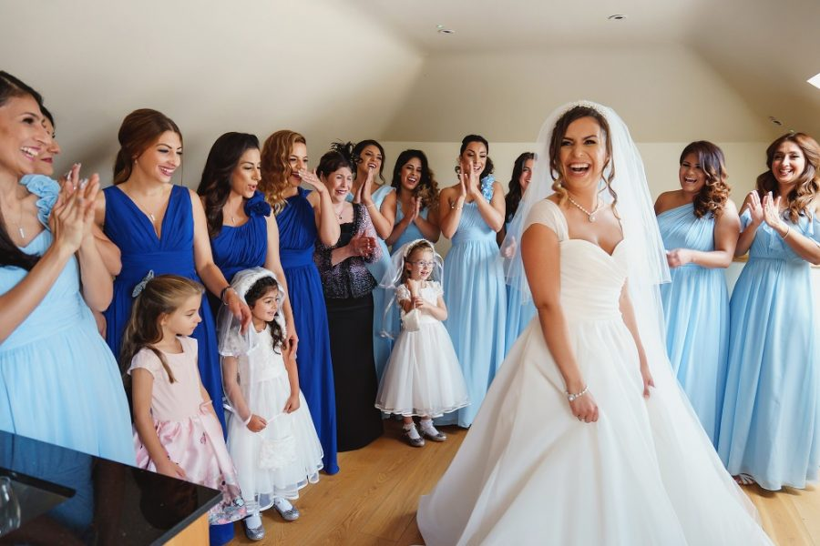 bride reveals her wedding dress to bridesmaids