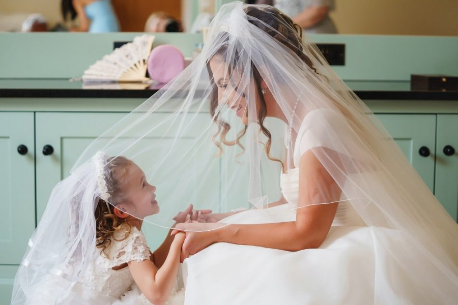 bride and flower girl holding hands