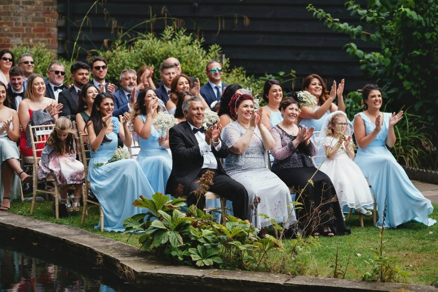 guests cheer and clap during wedding