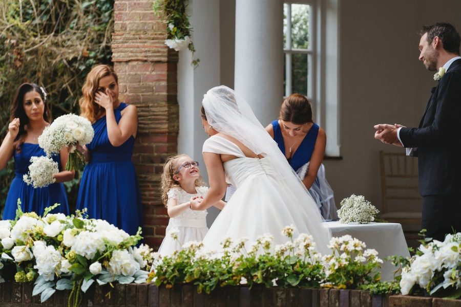 bride and flower girl holding hands during wedding
