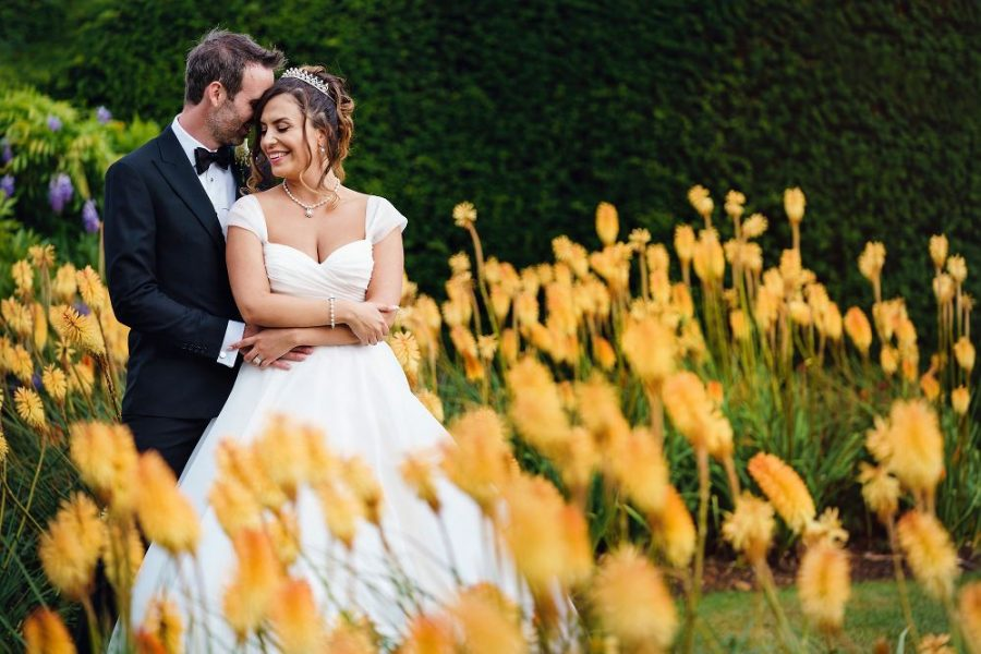 wedding couple cuddle in yellow flowers