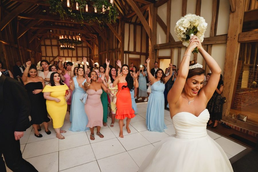 throwing the bouquet at barn wedding venue