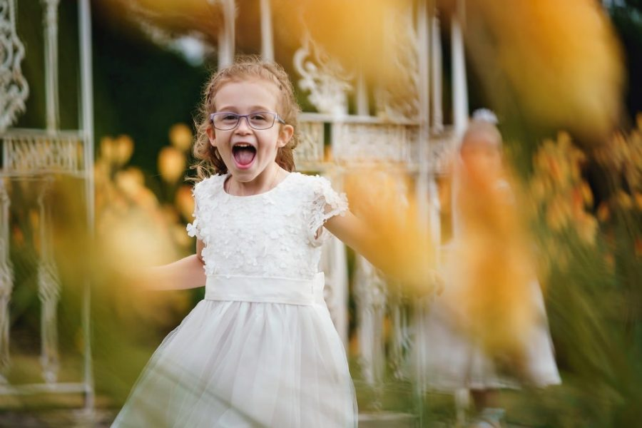 flower girl running through yellow flowers