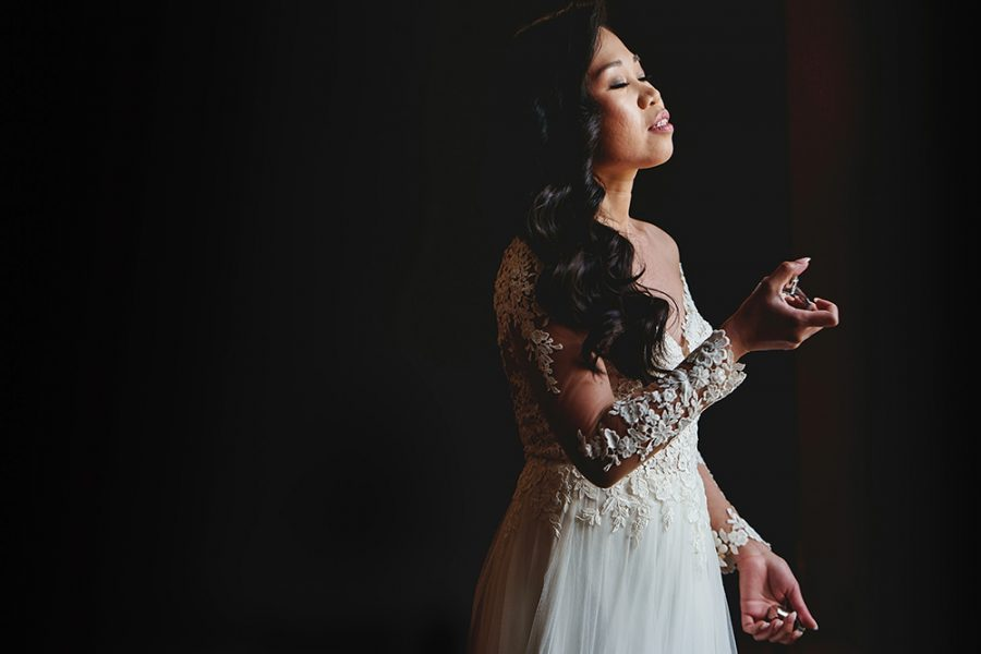 bride spraying perfume in beautiful window light