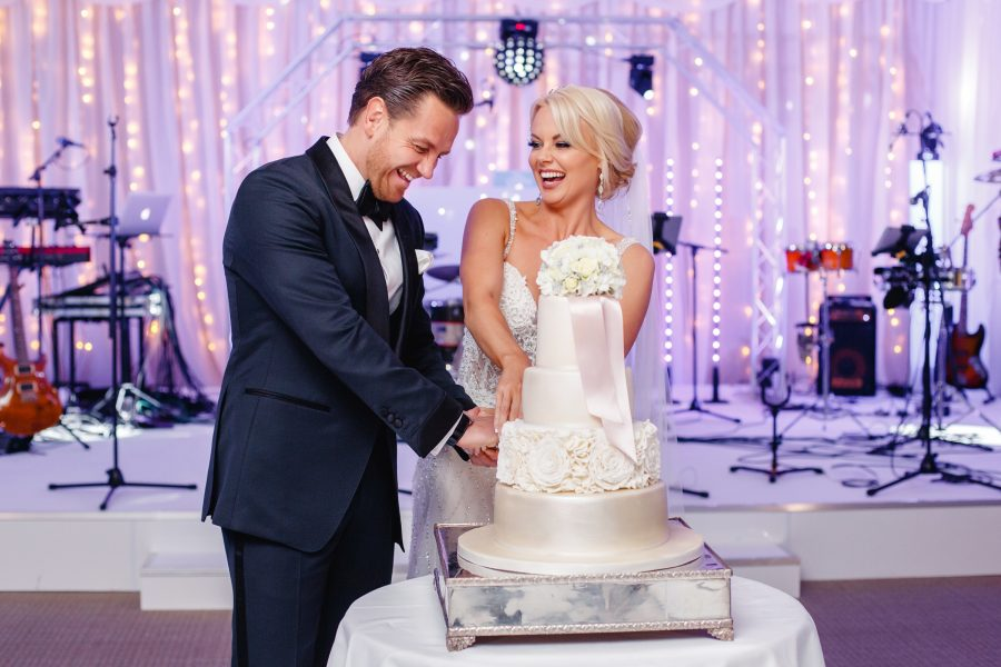COUPLE CUTTING THEIR CAKE AT THE GROVE