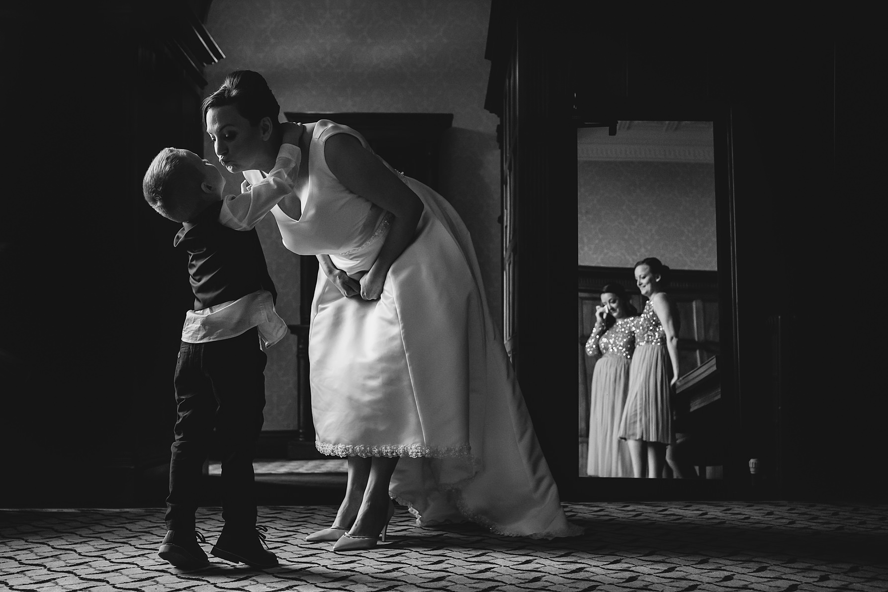 bride kissing son whilst bridesmaids get emotional
