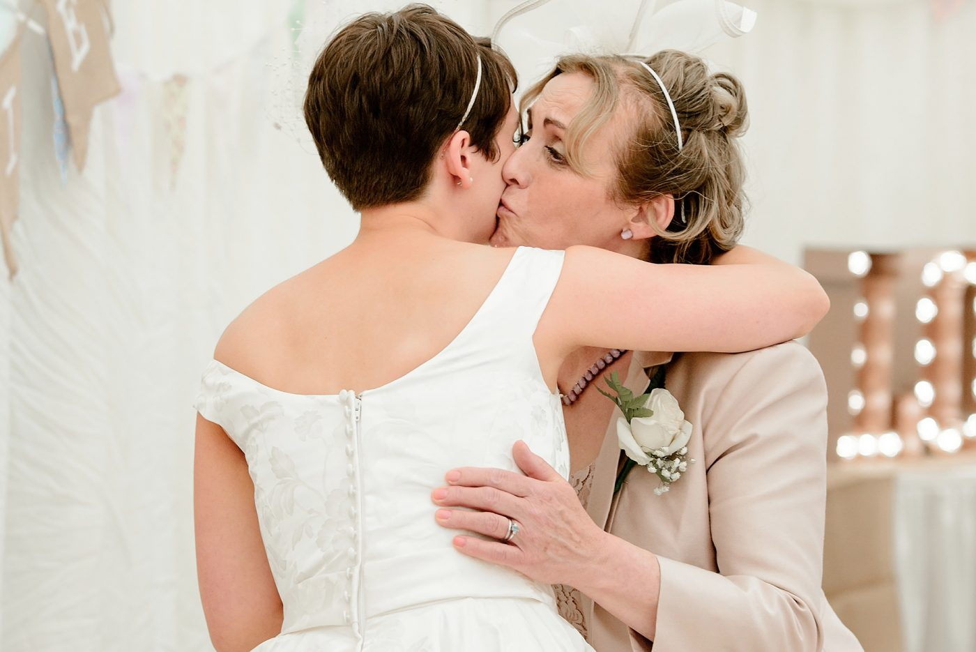 mother of the bride kisses daughter