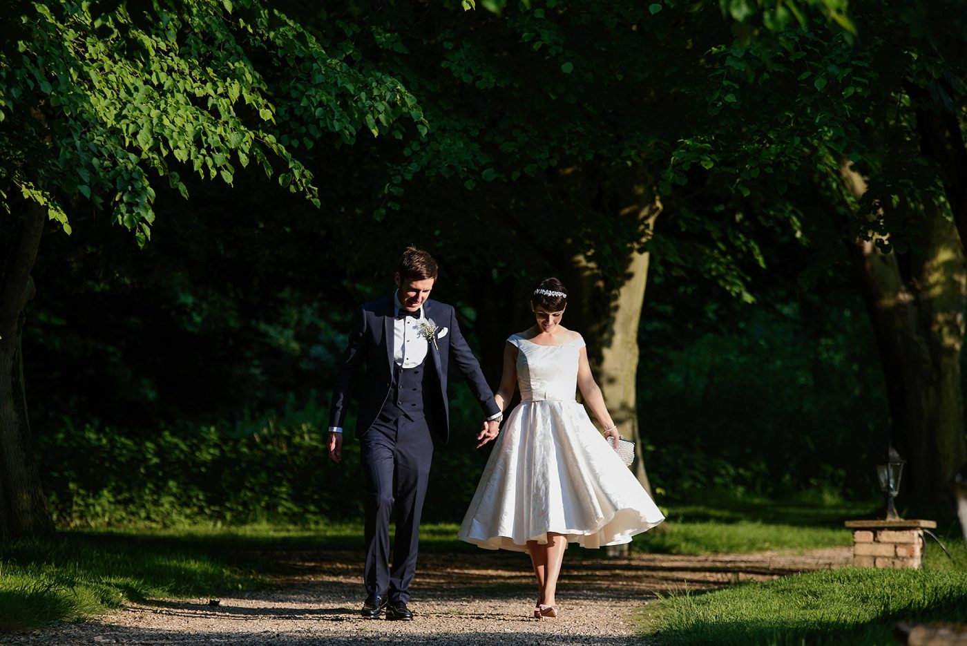 bride and groom holding hands and walking in the sun