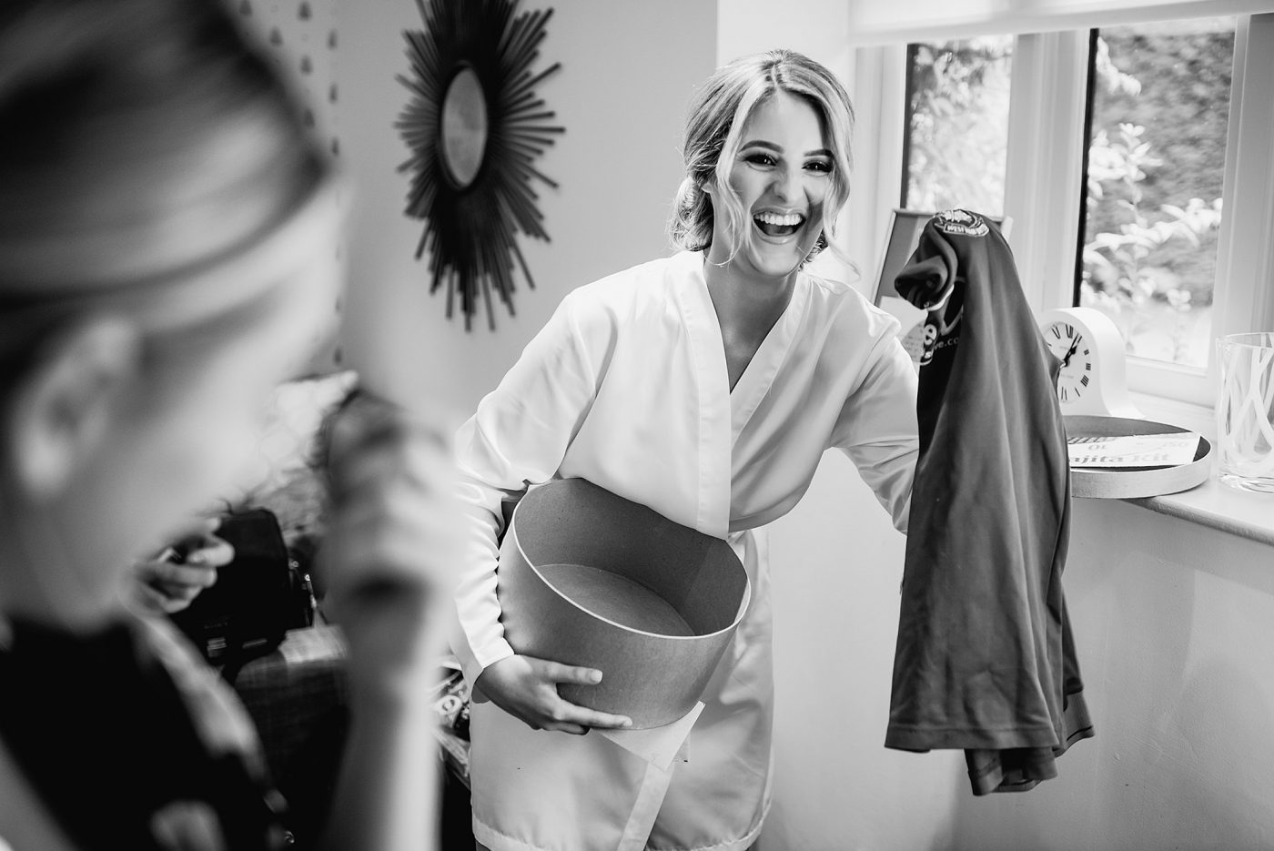 bride laughing as she opens football shirt present from groom