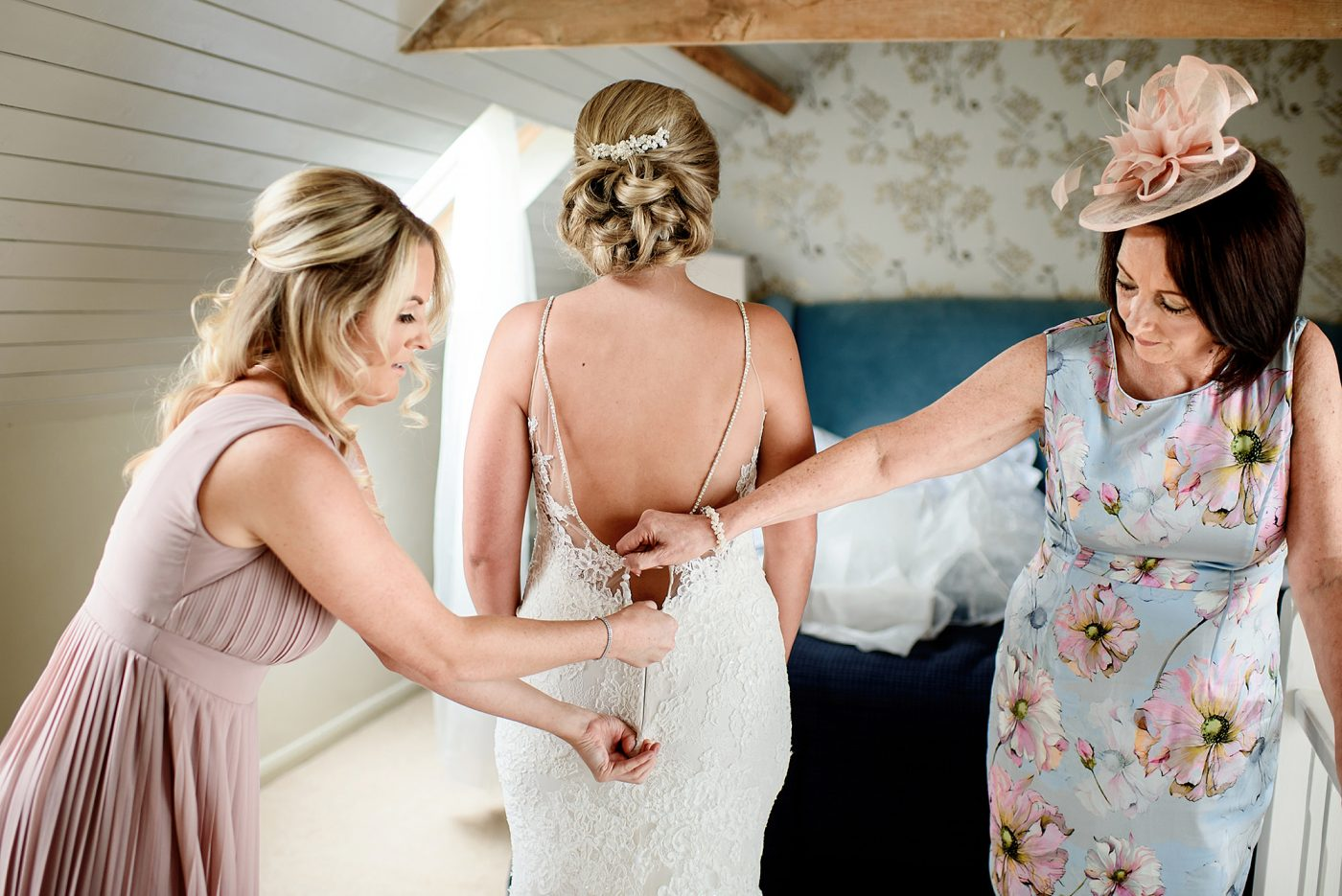 bridesmaids helping to do up the enzoani wedding dress