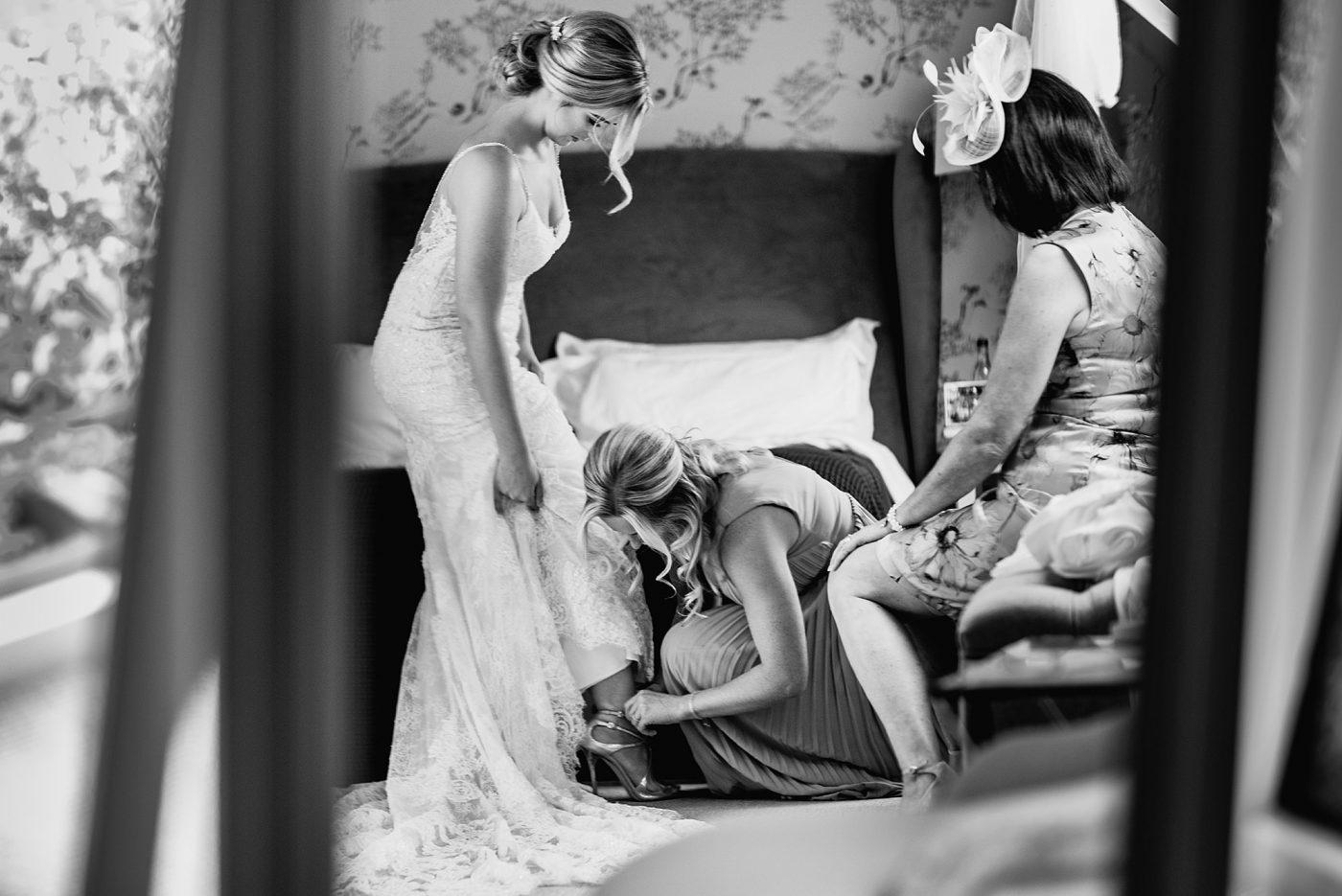 bridesmaids help put on Jimmy Choo shoes