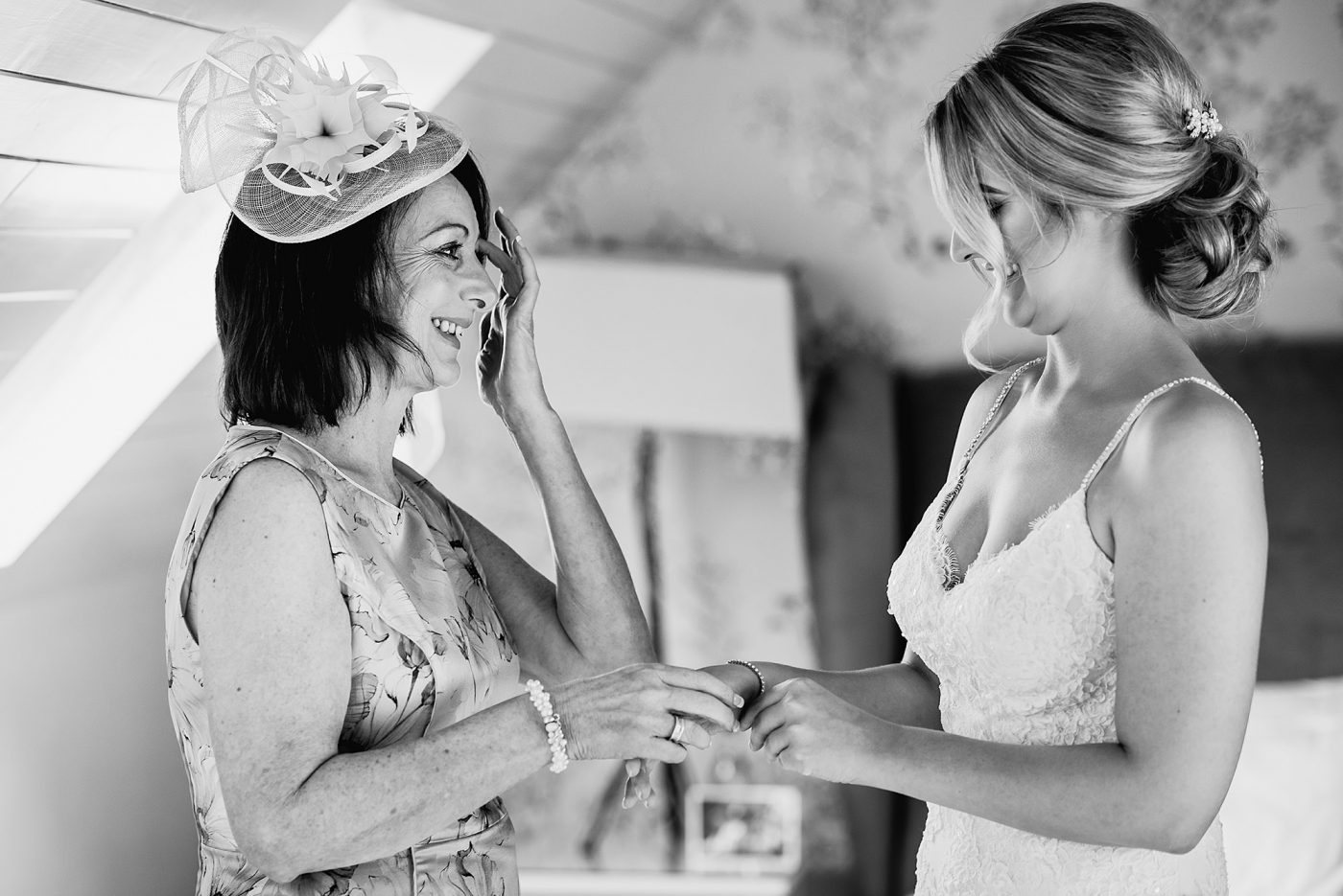 mother of the bride helps put on jewelry