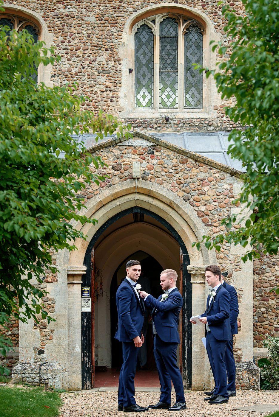 ushers adjusting groom's buttonhole