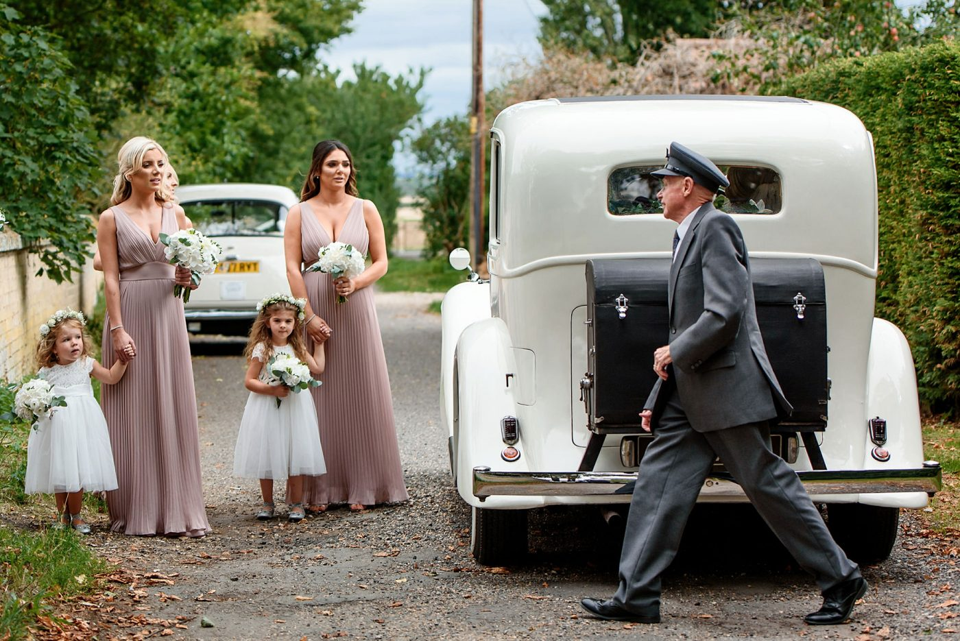 wedding party arrive in a classic white car