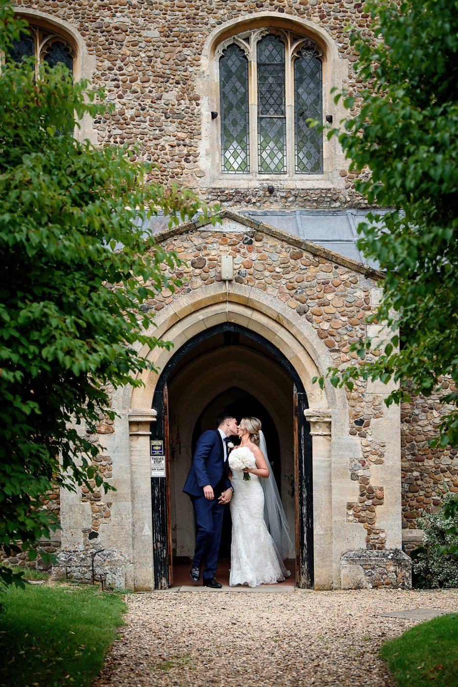 bride and groom kiss at comberton church