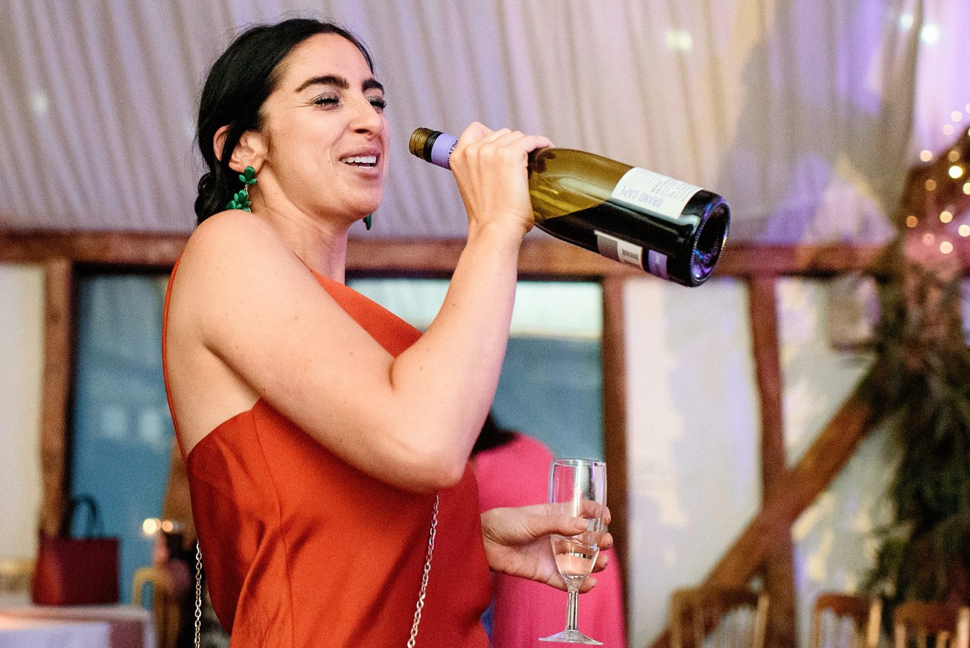 guest singing into wine bottle