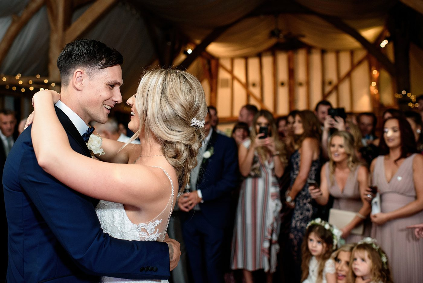 bride and groom have their first dance in barn
